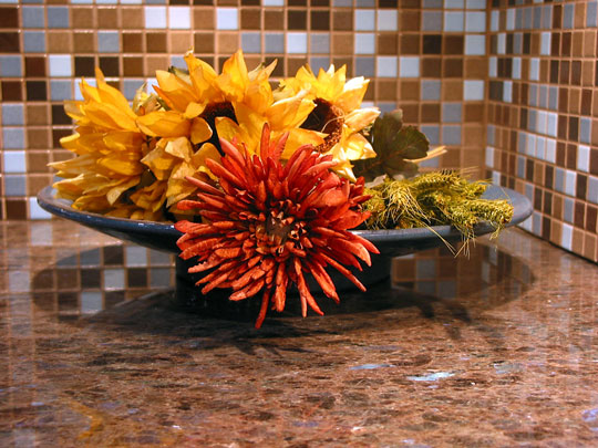 granite countertop with a bowl of colorful flowers